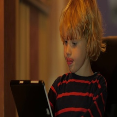 A cute little child uses a tablet PC at a table at home. Stock Footage
