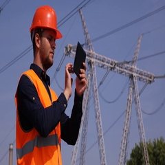 Engineer Man Working on Digital Tablet near Wire Lines Network Electricity Pylon Stock Footage