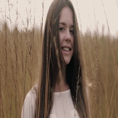 Young girl in a white blouse standing in the high yellow summer grass, gives a Stock Footage