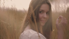 Young girl in a white blouse standing in the high yellow summer grass looking Stock Footage