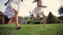 Two little girls in white dresses, with beautiful haircuts running and jumping Stock Footage