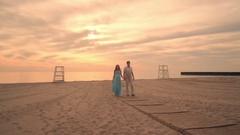 Love couple walking on sea beach at sunset. Pregnant couple on beach at sunset Stock Footage