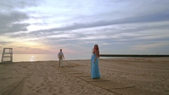 Man walking towards his pregnant wife. Romantic photo session on beach Stock Footage