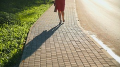 Red-haired girl walking through the city at sunset Stock Footage