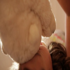 Cute little European girl is playing with teddy bear, hugging it, than kissing Stock Footage