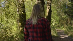 Steadicam Shot Of Woman Walking Through Forest, She Touches Large Trees Stock Footage