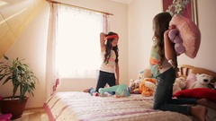 Happy little girls having fun throwing to each other soft toys in the nursery Stock Footage