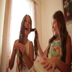 Two laughing girls sitting on the bed in front of a window, one girl makes a Stock Footage