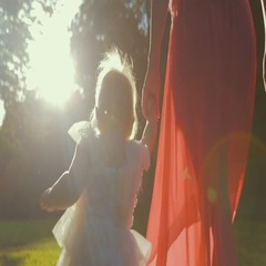 Baby in a puffy white dress makes first steps holding mother hand in a bright Stock Footage