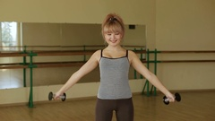 Young slender girl doing exercise with dumbbells. Fitness. Lifting weights. Stock Footage
