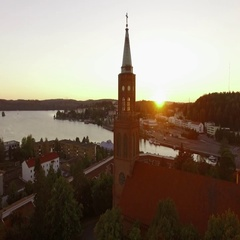 Aerial shot of the setting sun blinking through church tower windows in Stock Footage