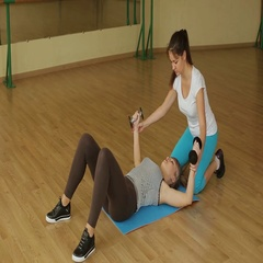 Young healthy girl is engaged with dumbbells with a personal trainer. Stock Footage