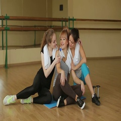 Three beautiful girls are sitting in the training room and rest after a workout. Stock Footage