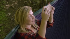 Young Woman Relaxes In Hammock And Takes Photos With Her Smartphone Stock Footage