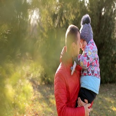 Dad in a red jacket holding his little daughter on his arms. Stock Footage
