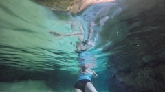 A woman swimming in an underground cave cenote in Mexico Stock Footage