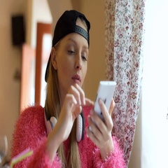 Pretty, stylish girl wearing baseball cap and browsing internet on smartphone Stock Footage