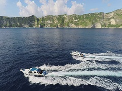 Aerial shot of speed boats cruising along the steep cliffs of Nusa Penida Stock Footage