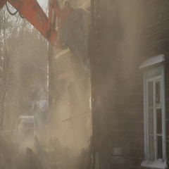 Close-up of an excavator breaks the wooden building and the dust rises Stock Footage