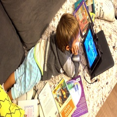 Top view on child watching tablet on sofa Stock Footage