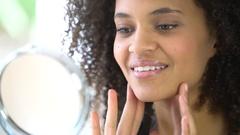 Beautiful mixed-race woman putting makeup on Stock Footage