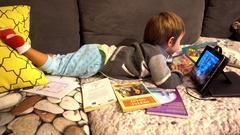 Kid moves books away and watches tablet Stock Footage
