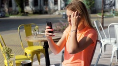 Happy, beautiful girl checking her appearance in smartphone Stock Footage