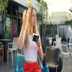 Pretty, blonde girl doing photos on old camera in the outdoor cafe Stock Footage