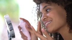 Portrait of beautiful mixed-race woman applying cosmetics on her face Stock Footage