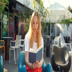 Girl receives message on smartphone while reading a book in the outdoor cafe Stock Footage