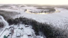 Drone flying over the frosty village to the bend of the river. Winter season Stock Footage