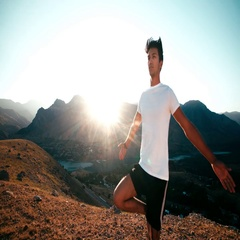 Young Asian man doing yoga in a mountain area, healthy life, sun glare, slow Stock Footage