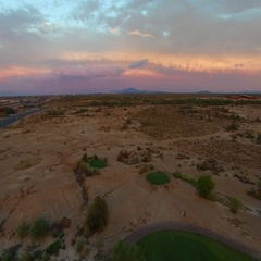 4K Aerial Drone Desert Golf Course Fly Backwards Reveal Green Colorful Clouds Stock Footage