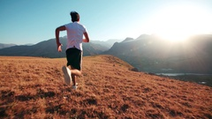 Young Indian guy doing a morning jog through mountainous terrain, slow motion Stock Footage
