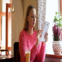 Pretty girl in fluffy sweater browsing internet on tablet and smiling to the cam Stock Footage