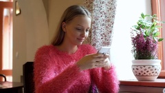 Happy girl in pink, fluffy sweater texting messages on smartphone Stock Footage