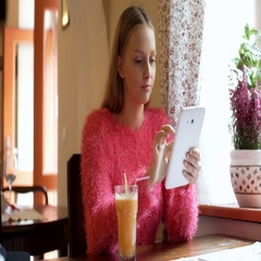 Pretty girl browsing internet on tablet while sitting in the cafe Stock Footage