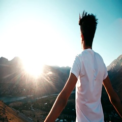 Young Asian male reaching to the top of the mountain area, standing on top of a Stock Footage