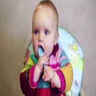 Baby girl sitting in a children's chair and playing with a spoon in the room Stock Footage