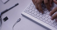 4K Angle of someone's hands typing on a keyboard on a desk Stock Footage