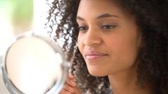 Beautiful mixed-race woman putting lipstick on Stock Footage