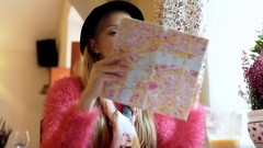 Girl wearing bowler hat and reading map while sitting in the cafe Stock Footage
