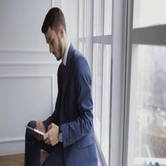 Coworker businessman using digital tablet sitting on windowsill Stock Footage