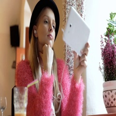 Girl looking happy while watching video on tablet in the cafe Stock Footage