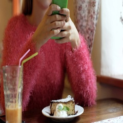 Girl using smartphone while sitting by the table in the cafe Stock Footage