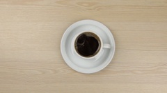 Approximation of hot steaming cup of coffee standing on a wooden table Stock Footage