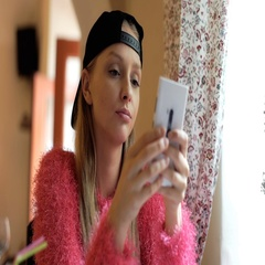 Calm girl wearing baseball cap and texting messages on smartphone Stock Footage