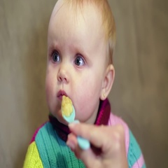 Baby girl eating from a spoon baby food, which gives him the mother Stock Footage