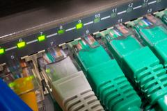 Close up of green network cables connected to switch glowing Stock Photos