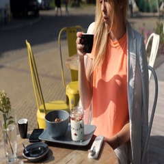 Relaxed girl drinking coffee and having breakfast in the outdoor cafe, steadycam Stock Footage